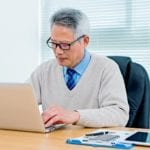 Elderly Asian man at his desk working at laptop