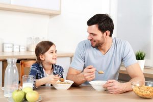 Girl and father eating cereal at kitchen table