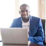Portrait of happy young African businessman looking at camera with computer, Nigeria, Africa.