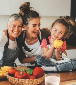3 generations of women are smiling at the kitchen table with vegetables