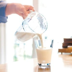Pouring milk from a can into a glass on the table